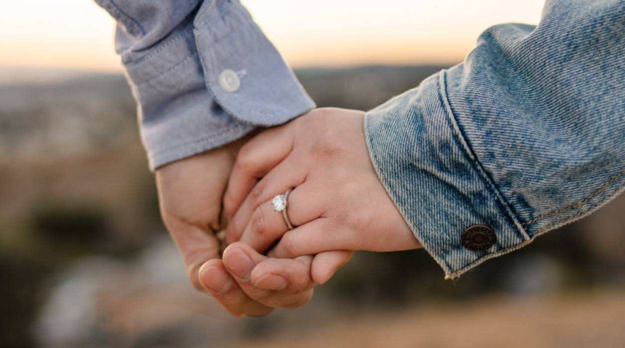 Holding hands. Woman wears a diamond ring.