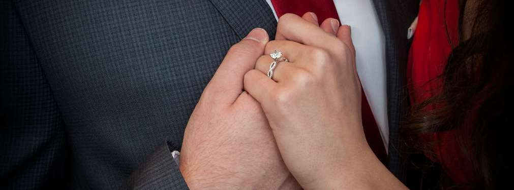Holding hands. Woman wears a cushion cut diamond ring.